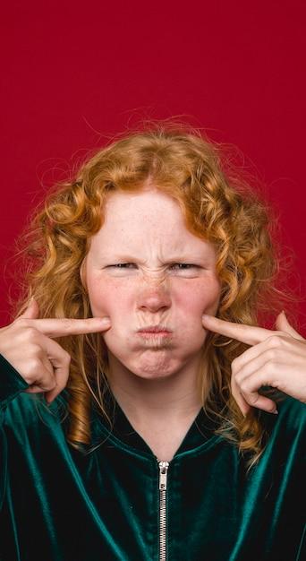 Mulher jovem engraçado gengibre fazendo careta Foto gratuita