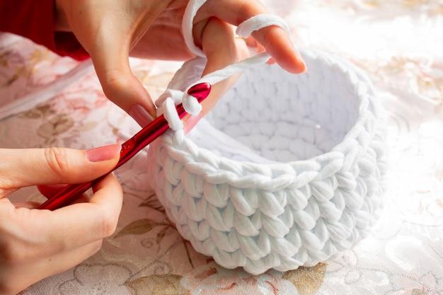 Mulher jovem enquanto faz crochê com fios de t-shirt. Foto Premium