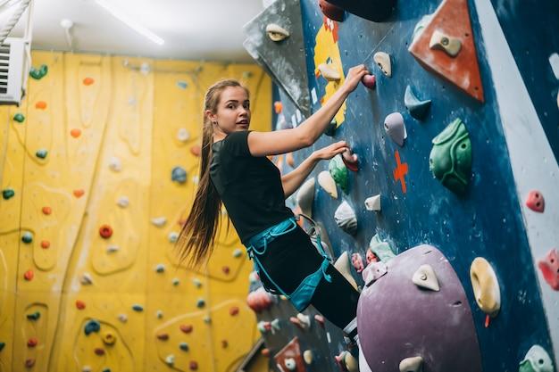 Mulher jovem, escalando, um, alto, indoor, parede artificial, escalada Foto gratuita