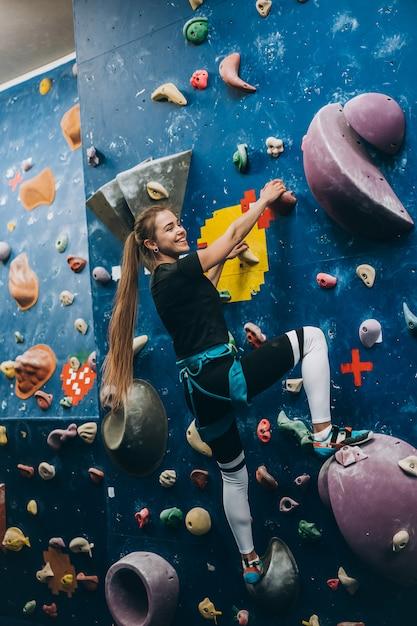 Mulher jovem escalando uma parede alta de escalada artificial interna Foto gratuita