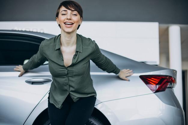 Mulher jovem escolhendo um carro em um showroom Foto gratuita