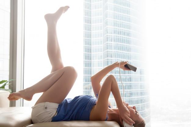 Mulher jovem, escutar, música smartphone, em, fones, mentindo sofá Foto gratuita