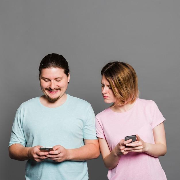 Mulher jovem, espiando, e, espiando, em, smartphone, de, dela, namorado, usando, telefone móvel Foto gratuita