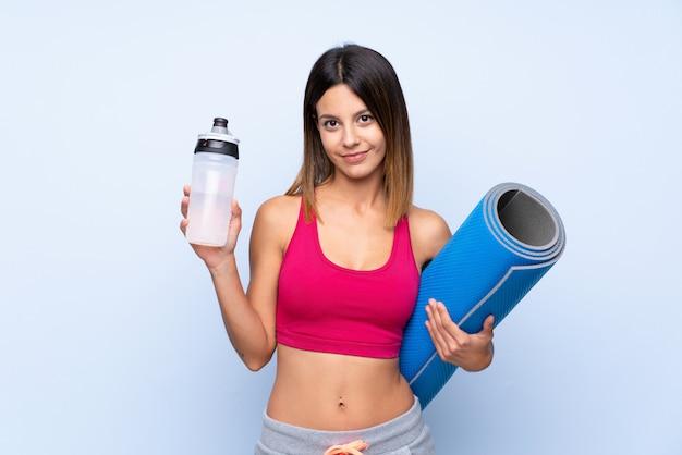 Mulher jovem esporte sobre parede azul isolada com garrafa de água de esportes e com uma esteira Foto Premium