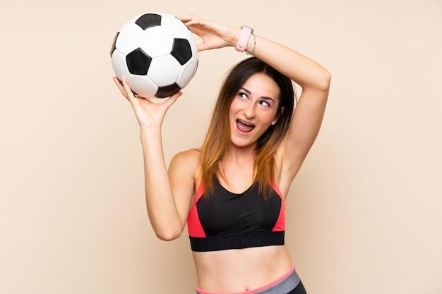 Mulher jovem esporte sobre parede isolada, segurando uma bola de futebol Foto Premium