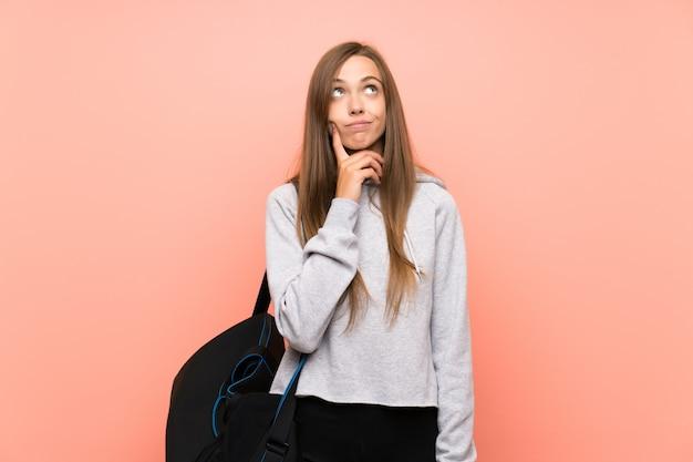 Mulher jovem esporte sobre parede rosa isolada, pensando uma idéia Foto Premium