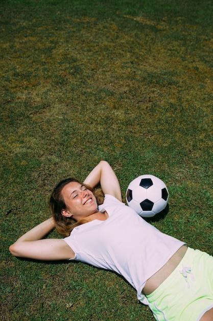 Mulher jovem esportiva descansando no campo de futebol Foto gratuita