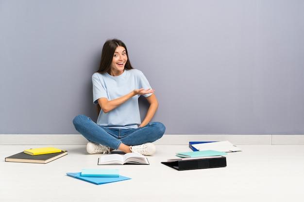 Mulher jovem estudante com muitos livros no chão, estendendo as mãos para o lado para convidar para vir Foto Premium
