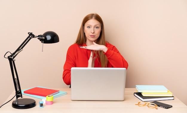 Mulher jovem estudante em um local de trabalho com um laptop, fazendo gesto de intervalo Foto Premium