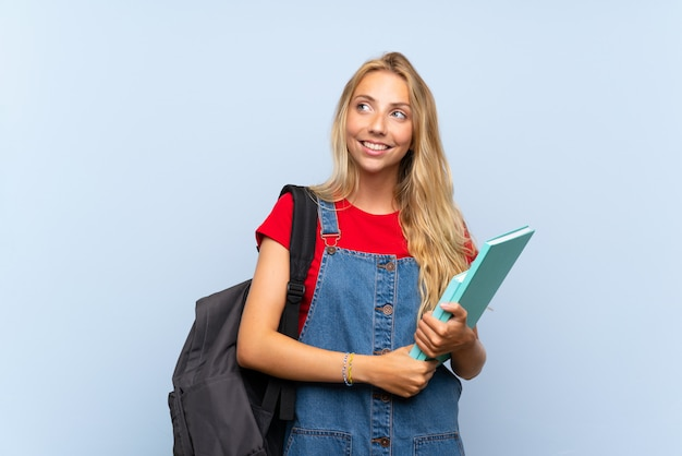Mulher jovem estudante loira sobre parede azul isolada, rindo e olhando para cima Foto Premium