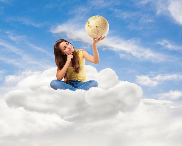 Mulher jovem estudante olhando-o globo do mundo sentado em uma nuvem Foto gratuita