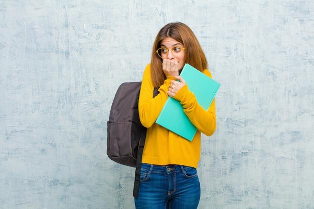 Mulher jovem estudante olhando preocupado, ansioso, estressado e com medo, roer unhas e olhando para o espaço da cópia lateral contra a parede da parede do grunge Foto Premium