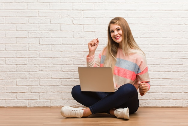 Mulher jovem estudante russo sentado dançando e se divertindo Foto Premium