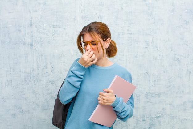 Mulher jovem estudante sentindo nojo, segurando o nariz para evitar cheirar um fedor sujo e desagradável contra a parede do grunge Foto Premium