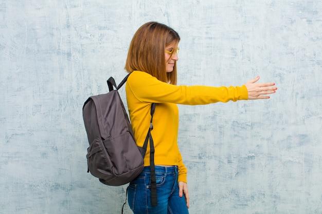 Mulher jovem estudante sorrindo, cumprimentando e oferecendo um aperto de mão para fechar um negócio bem sucedido, conceito de cooperação contra o fundo da parede do grunge Foto Premium