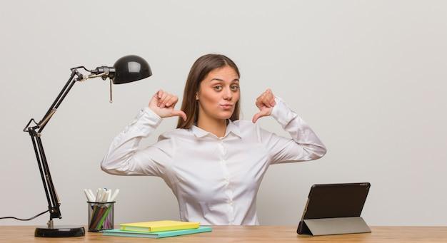 Mulher jovem estudante trabalhando na mesa dela apontando os dedos, exemplo a seguir Foto Premium