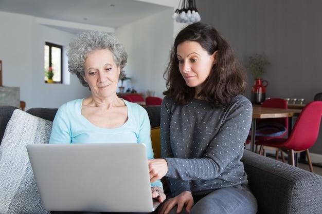 Mulher jovem, explicando, vovó, como, uso, laptop Foto gratuita