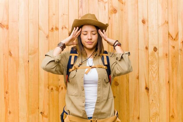 Mulher jovem explorador latino contra o fundo da parede de madeira Foto Premium