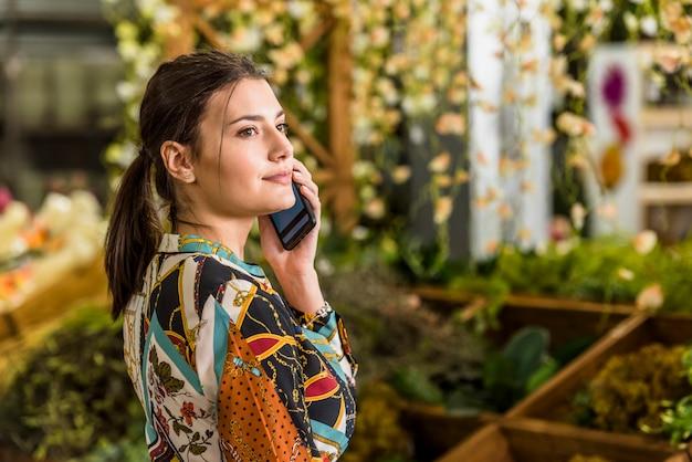 Mulher jovem, falando, por, telefone, em, casa verde Foto gratuita