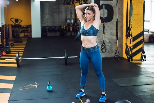 Mulher jovem, fazendo, esticando exercício, em, ginásio Foto gratuita