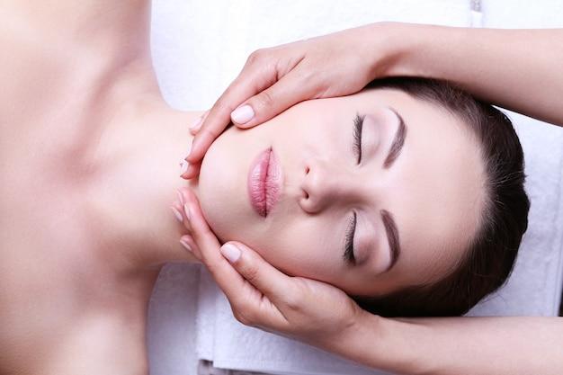 Mulher jovem fazendo massagem facial Foto gratuita