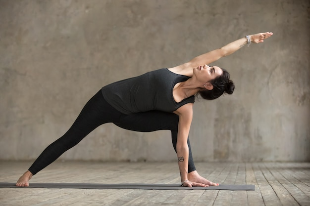 Mulher jovem, fazendo, utthita, parsvakonasana, exercício Foto gratuita