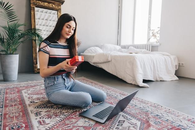 Mulher jovem feliz abrindo o presente na frente do laptop durante a videochamada ou bate-papo, comemorando o aniversário online. Foto Premium