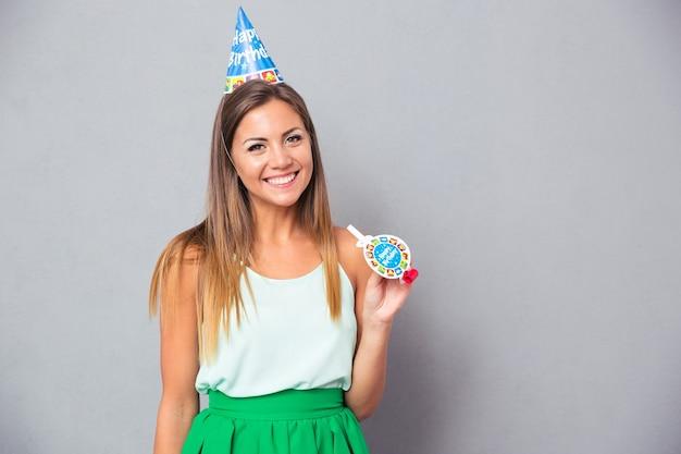 Mulher jovem feliz com chapéu e apito de aniversário Foto Premium