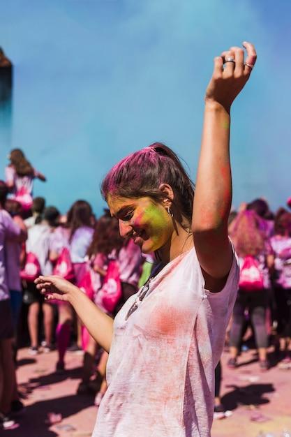 Mulher jovem feliz dançando na celebração holi Foto gratuita