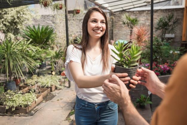 Mulher jovem feliz dando planta em vaso para seu cliente em estufa Foto gratuita