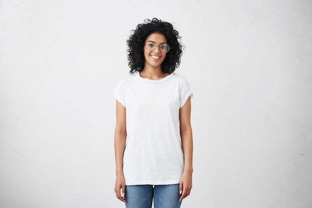 Mulher jovem feliz, de pé na parede branca em branco Foto gratuita