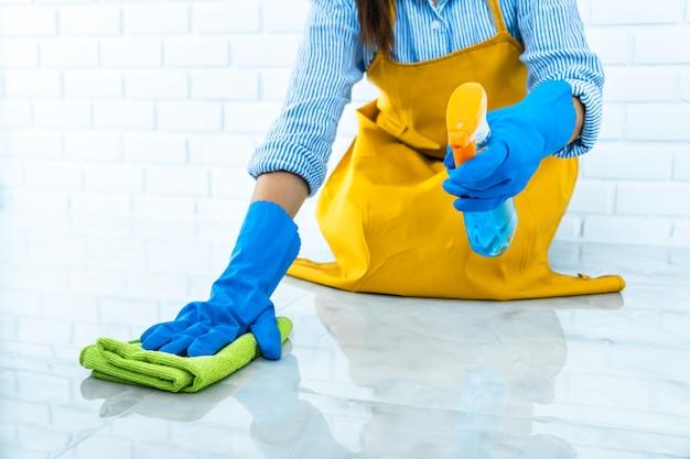Mulher jovem feliz em borracha azul usando pano durante a limpeza no chão em casa Foto Premium