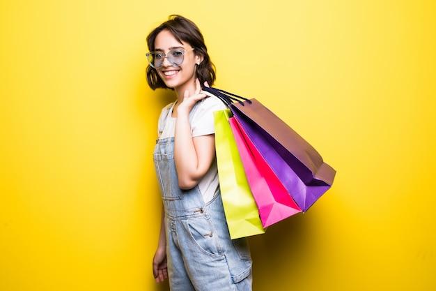 Mulher jovem feliz em óculos de sol segurando sacolas de compras. Foto gratuita