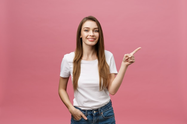 Mulher jovem feliz em pé e apontando o dedo isolado sobre fundo rosa Foto Premium