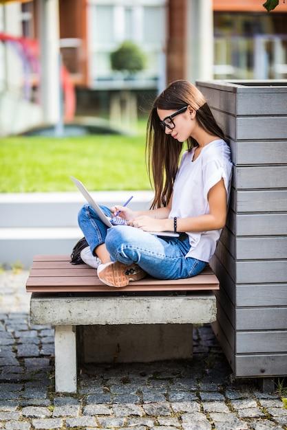 Mulher jovem feliz em roupa casual e óculos usando laptop moderno e fazendo anotações enquanto está sentado no banco na rua da cidade Foto gratuita