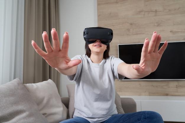 Mulher jovem feliz jogando em óculos vr interior, conceito de realidade virtual com jovem se divertindo com óculos de ouvido, Foto Premium