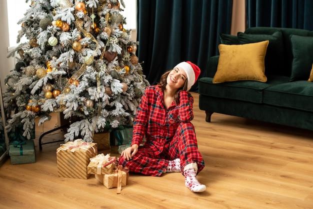 Mulher jovem feliz jogando um presente perto da árvore de natal. ela está sentada perto de presentes e presentes. tendências em cores fortuna ouro e verde maré. Foto Premium