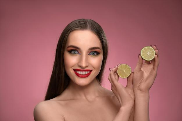 Mulher jovem feliz mostra limão benefício para a saúde, segurando duas partes cortadas nas mãos parecendo encantador Foto Premium