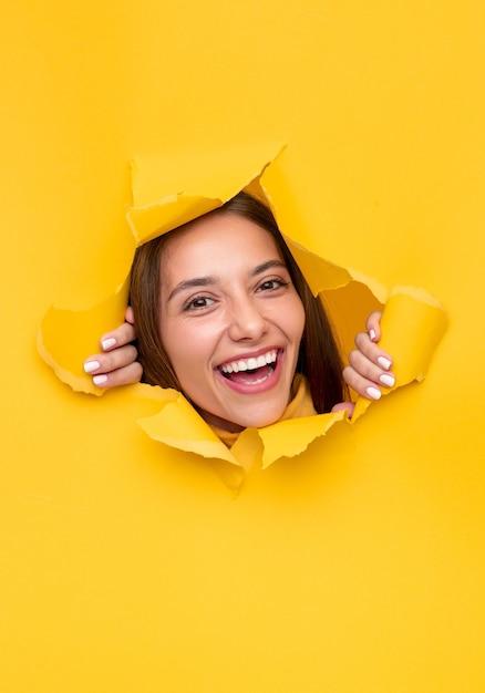 Mulher jovem feliz olhando para a câmera e rindo, rasgando um buraco em papel amarelo brilhante Foto Premium