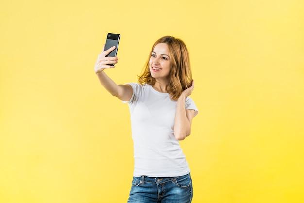 Mulher jovem feliz tomando selfie no telemóvel contra o fundo amarelo Foto gratuita