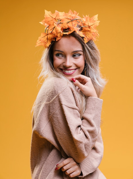 Mulher jovem feliz vestindo tiara e posando contra parede amarela Foto gratuita