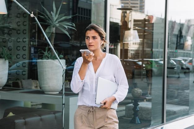 Mulher jovem, ficar, em, a, edifício escritório, entrada, usando, comando voz, registrador Foto gratuita