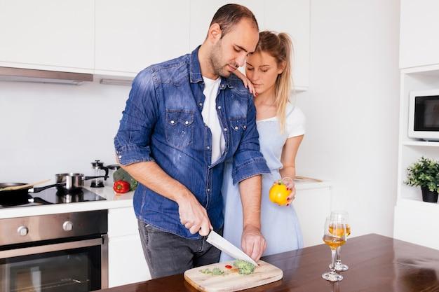 Mulher jovem, ficar, perto, a, marido, corte, a, bellpepper, com, faca, ligado, tabela, cozinha Foto gratuita