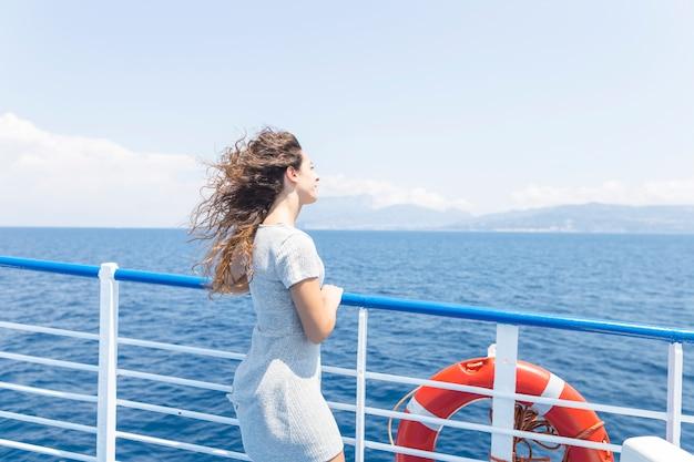 Mulher jovem, ficar, perto, a, navio, corrimão, olhar, a, azul, mar Foto gratuita