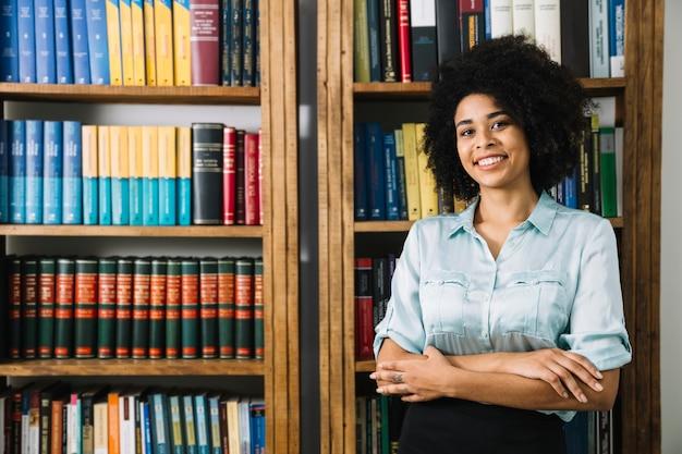 Mulher jovem, ficar, perto, estante de livros, em, escritório Foto gratuita