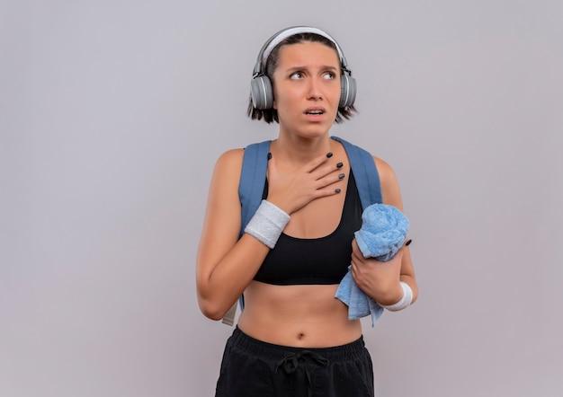 Mulher jovem fitness em roupas esportivas com mochila e fones de ouvido na cabeça, segurando uma toalha com a mão no peito, olhando de lado preocupada em pé sobre uma parede branca Foto gratuita