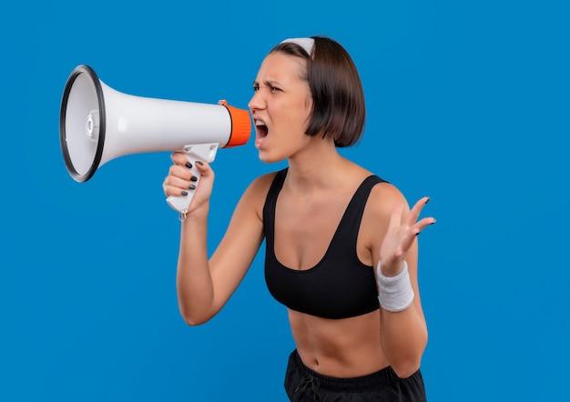 Mulher jovem fitness em roupas esportivas gritando para o megafone com expressão agressiva em pé sobre a parede azul Foto gratuita