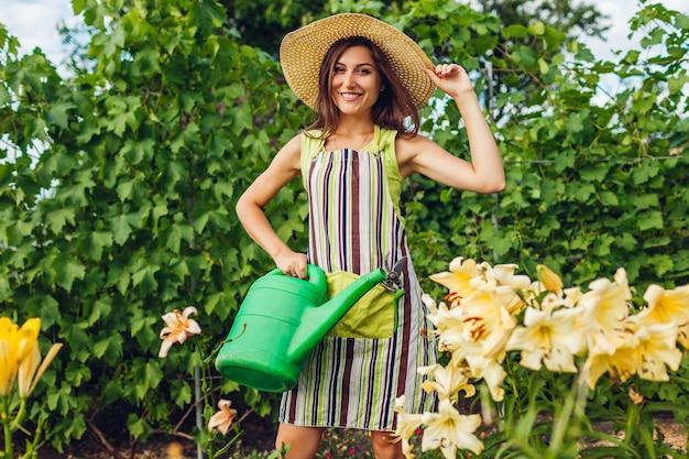 Mulher jovem, flores molhando, com, lata molhando, em, jardim Foto Premium