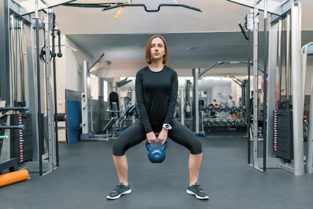 Mulher jovem forte aptidão com pesos pesados Foto Premium