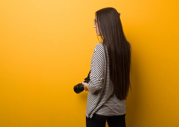 Mulher jovem fotógrafo por trás pensando em algo Foto Premium